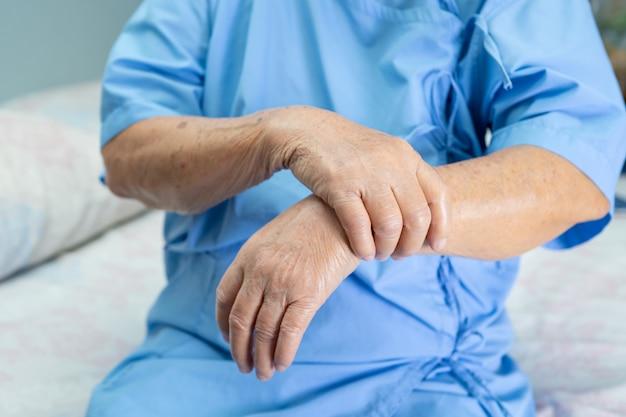 Asiatische ältere patientin fühlen schmerzen ihr handgelenk und arm im krankenhaus.