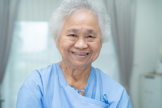Asiatische ältere patientin lächelt helles gesicht, während sie auf dem bett im krankenhaus sitzt