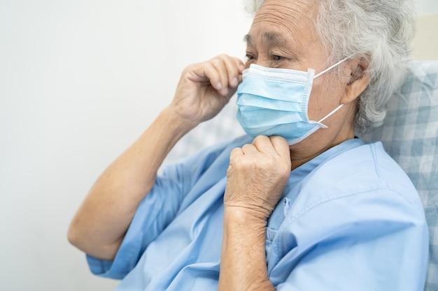 Asiatische ältere patientin mit maske zum schutz von coronavirus
