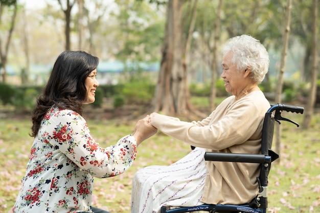 Asiatische ältere patientin mit sorgfalt auf rollstuhl im park