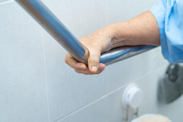 Asiatische ältere patientin verwenden toilettenbadgriff sicherheit im krankenhaus.
