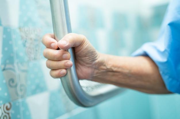 Asiatische ältere patientin verwendet steigungsgehweg-griffsicherheit mit hilfeunterstützung