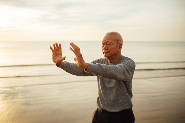 Asiatische ältere praxis des alten mannes tai chi und yoga werfen auf dem strandsonnenaufgang auf