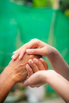 Asiatische ältere und asiatische junge händchenhalten.