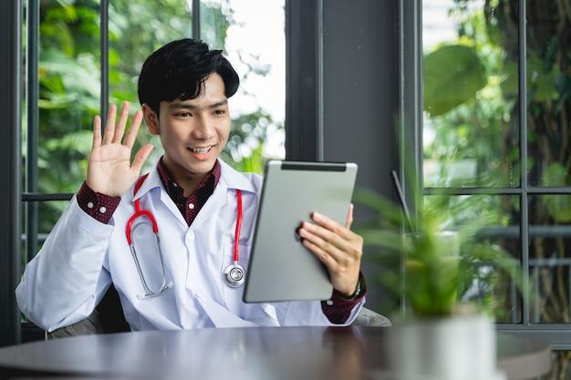 Asiatische ärzte verwenden tablets, um patienten per videoanruf zu begrüßen. eine neue medizinische normalität kann krankheiten behandeln, nachverfolgen und entfernte patienten über das internet der dinge konsultieren.