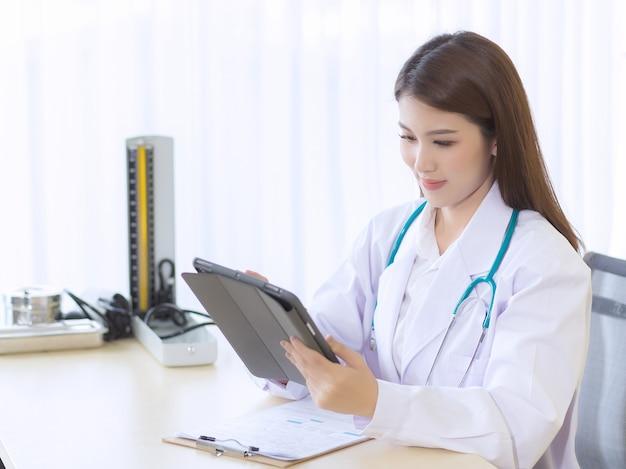 Asiatische ärztin arbeitsbericht ihrer patientin auf tablet