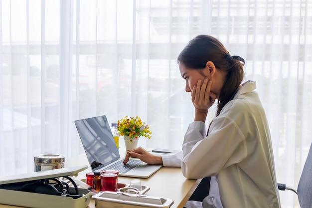 Asiatische ärztin beobachtete einen kopfschmerzjob in einem notizbuch