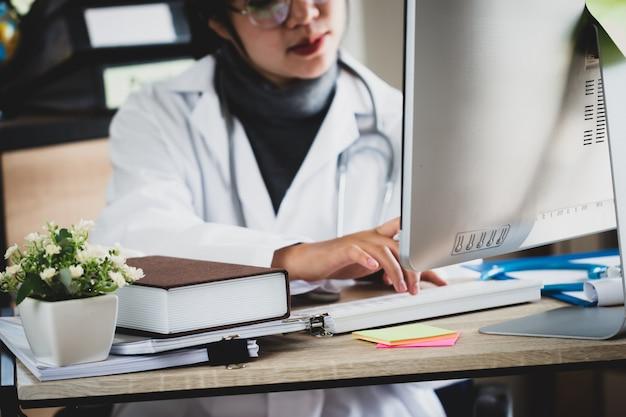 Asiatische ärztin der medizin, die am laptop in klinik mit stethoskop arbeitet