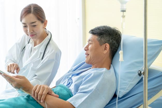 Asiatische ärztin, die auf krankenhausbett sitzt und mit älterem patienten sich bespricht