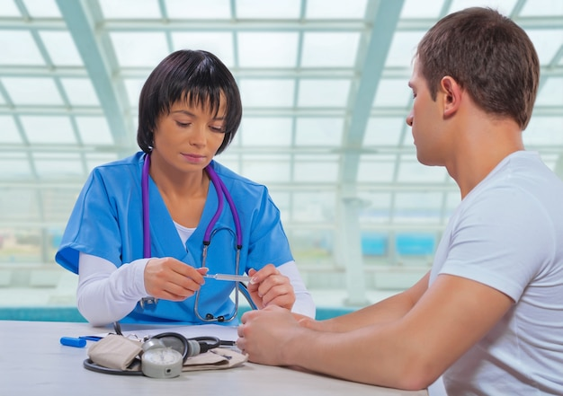 Asiatische ärztin, die auf medizinisches thermometer schaut und mit patient am tisch sitzt