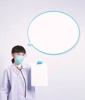 Asiatische ärztin, die ein leeres papier in der hand hält und platz kopiert, und sie trägt einen medizinischen handschuh