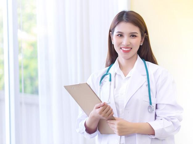 Asiatische ärztin, die ein weißes gewand und ein stethoskop trägt, interviewbogen