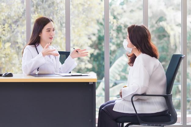 Asiatische ärztin, die einen medizinischen mantel trägt, spricht mit einer patientin, um eine behandlungsrichtlinie vorzuschlagen