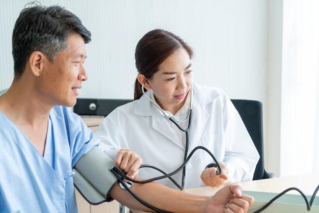 Asiatische ärztin, die ihre patientin überprüft