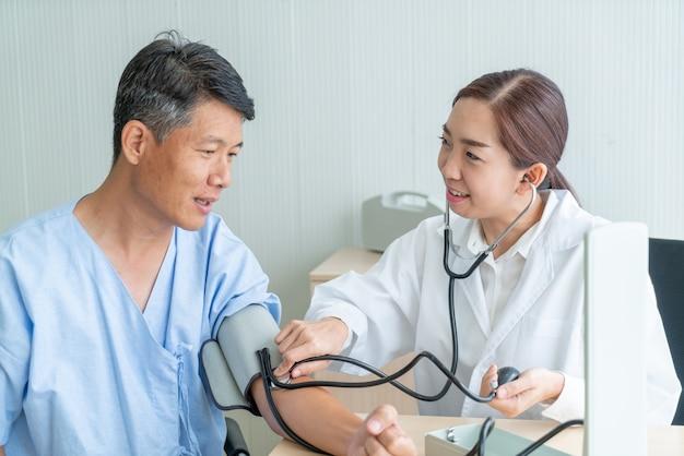 Asiatische ärztin, die ihren patienten prüft