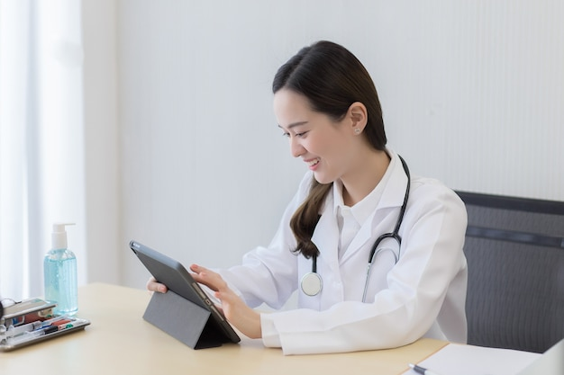 Asiatische ärztin, die informationen über patienten auf ihrem tablet mit glücklichem gesicht im büro sucht