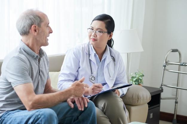 Asiatische ärztin, die mit älterem kaukasischem patienten während des hausbesuchs spricht