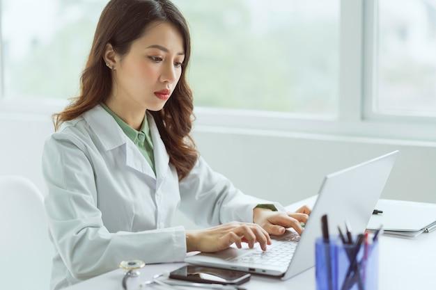 Asiatische ärztin, die mit computer im büro arbeitet