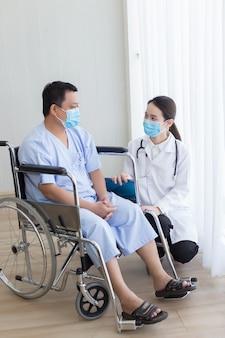 Asiatische ärztin fragt nach gesundheit mit einem patienten, der im krankenhaus im rollstuhl sitzt