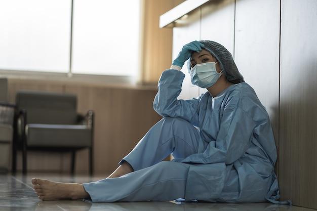 Asiatische ärztin mit chirurgischer gesichtsmaske, die auf dem boden sitzt, müde von der arbeit, weil die auswirkungen des ausbruchs der covid-19-pandemie, traurigkeit im gesundheitswesen, medizinisches und gesundheitskonzept