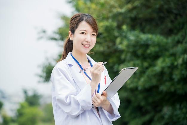 Asiatische ärztin mit medizinischer karte und stift