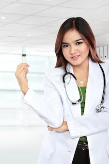 Asiatische ärztin trägt einen weißen kittel und ein stethoskop, das mit spritze aufwirft