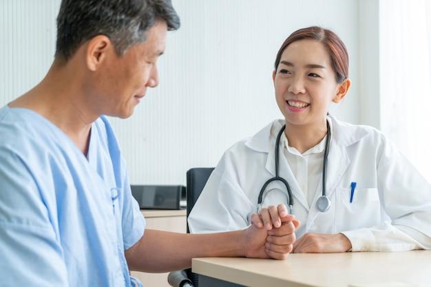 Asiatische ärztin und patient, die etwas beim sitzen am tisch bespricht