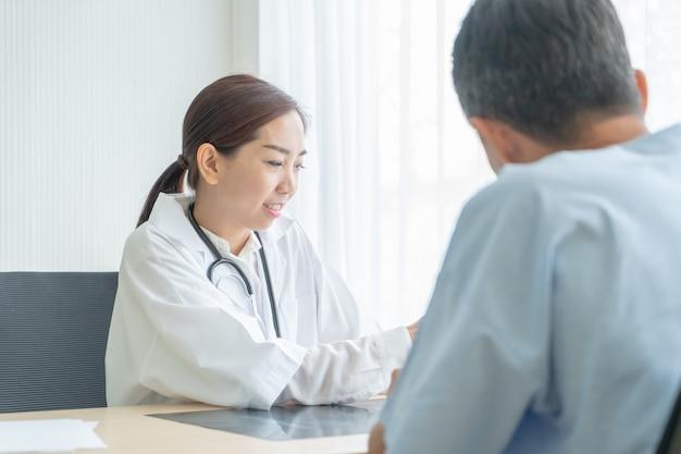 Asiatische ärztin und patientin, die etwas beim sitzen am tisch bespricht