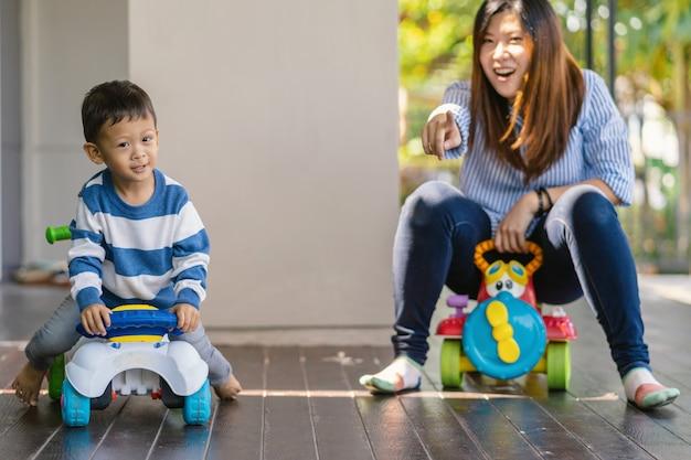 Asiatische alleinerziehende mutter mit sohn spielen mit autospielzeug zusammen, wenn sie im modernen haus leben