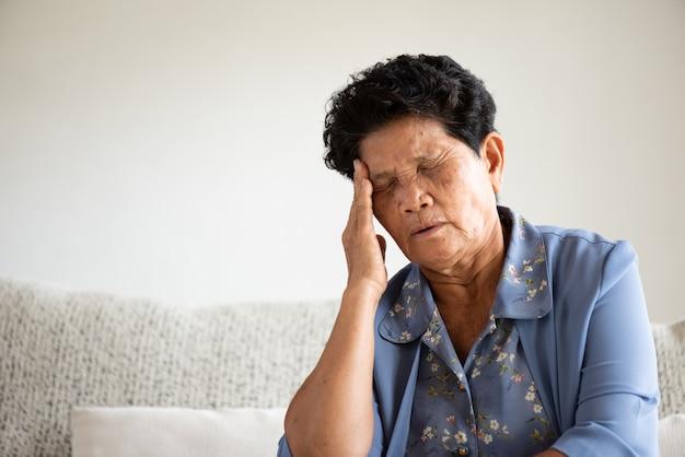 Asiatische alte frau, die auf sofa sitzt und kopfschmerzen hat