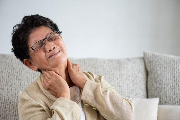 Asiatische alte frau, die auf sofa sitzt und nackenschmerzen hat
