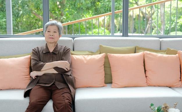 Asiatische alte frau, die auf sofa zu hause ruht