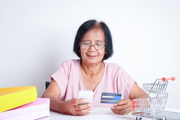 Asiatische alte frau, die kreditkarten für online-einkauf hält.