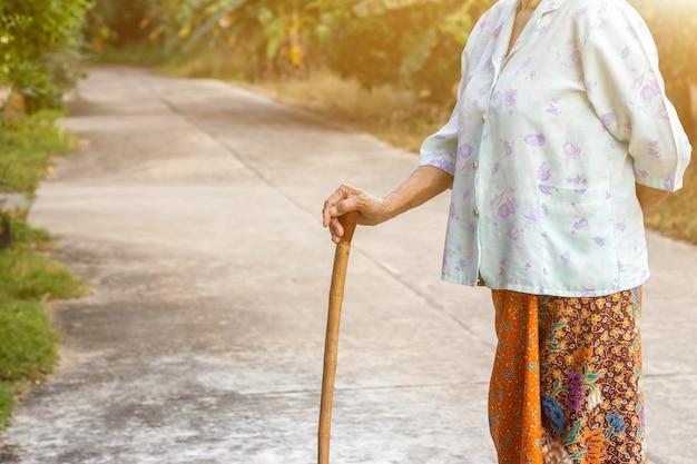 Asiatische alte frau, die mit ihren händen auf einem gehstock steht