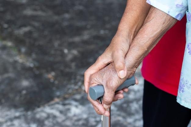 Asiatische alte frau, die mit ihrer hand auf einem gehstock mit der hand der tochter steht