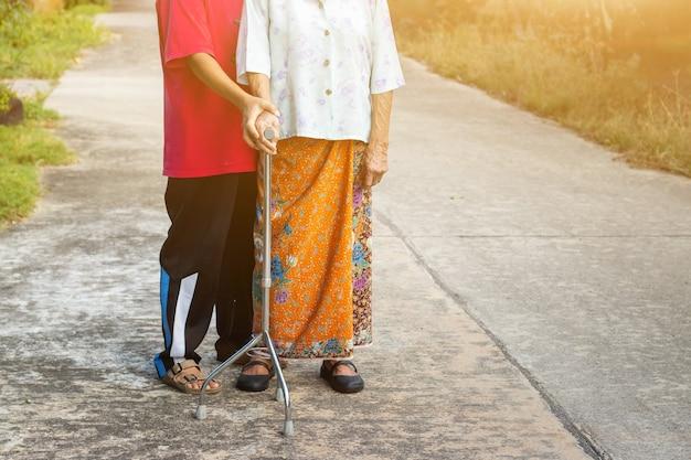 Asiatische alte frau, die mit ihrer hand auf einem wanderer mit der hand der tochter steht