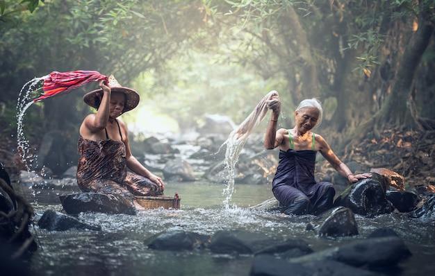 Asiatische alte frauen, die kleidung am nebenfluss waschen
