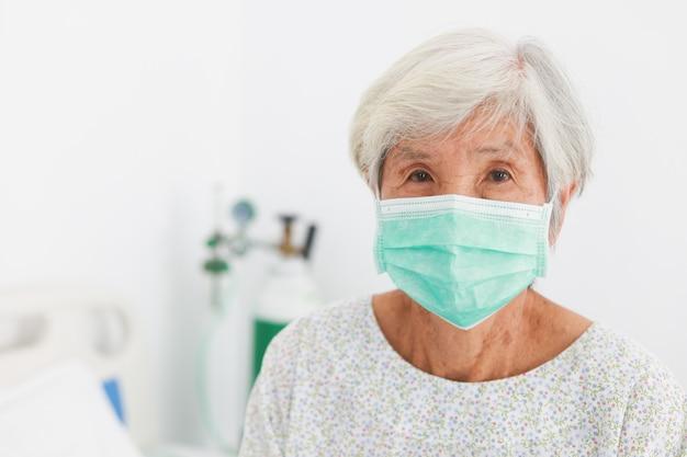 Asiatische alte geduldige frau mit maskenkrankheit im krankenzimmer mit virusgrippe