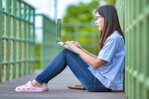 Asiatische arbeitende frau im öffentlichen park unter verwendung des laptops