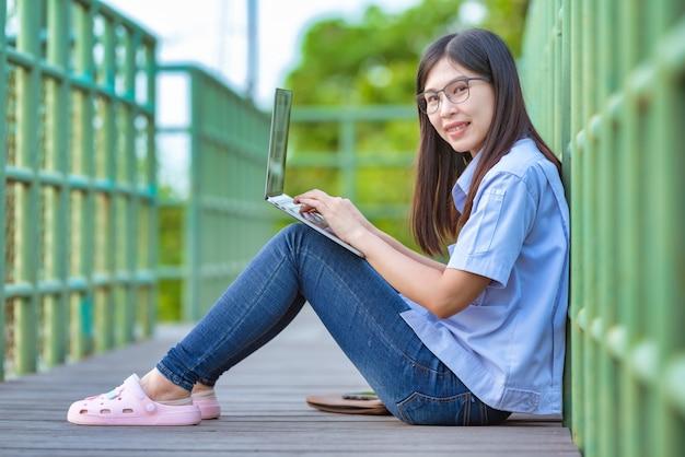 Asiatische arbeitende frauen im öffentlichen park unter verwendung des modernen lebensstils des laptops