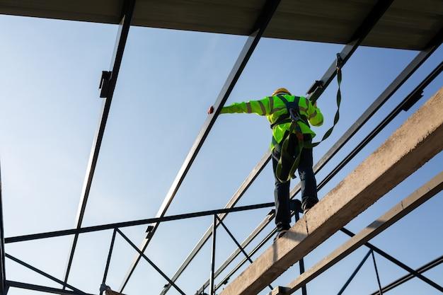 Asiatische arbeiter tragen sicherheitsausrüstung, um das dach auf der baustelle zu installieren. absturzsicherungsvorrichtung für arbeiter mit haken für sicherheitsgurt.