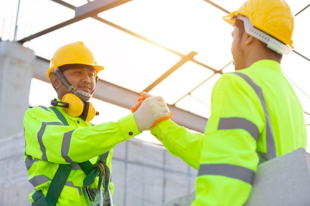 Asiatische arbeiter tragen sicherheitshöhenausrüstung, teamarbeit, partnerschaft, geste und personenkonzept - nahaufnahme von bauherrenhänden in handschuhen, die sich gegenseitig mit händedruck auf der baustelle begrüßen