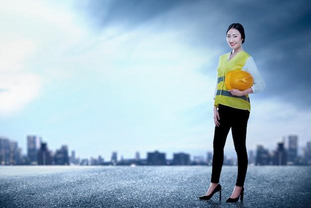 Asiatische arbeiterfrau, die gelben helm stehend hält