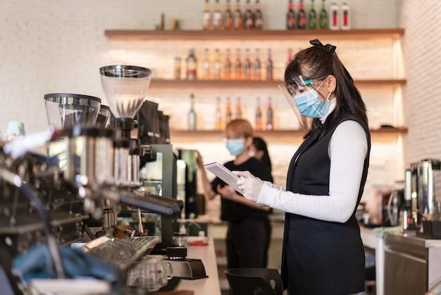Asiatische arbeiterin, die chirurgische maske und gesichtsschutz am kaffeehaus trägt