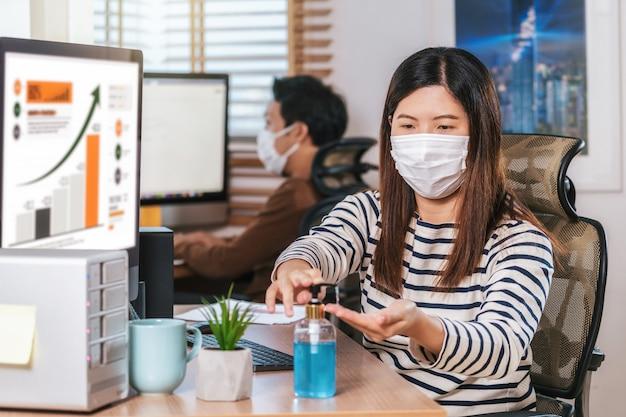 Asiatische arbeiterin, die händedesinfektionsmittel zum reinigen ihrer hand verwendet, wenn sie mit dem computer arbeitet