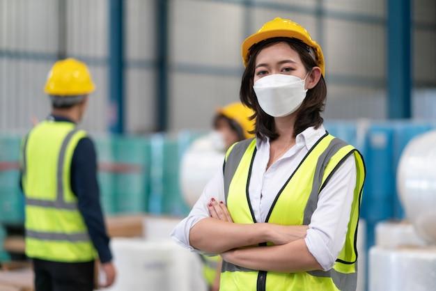 Asiatische arbeiterinnen tragen eine coronavirus-schutzmaske mit helmsicherheit in der lagerfabrik