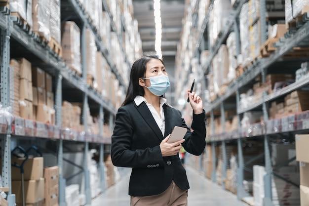 Asiatische arbeiterinnen tragen maskenarbeit während der covid19-pandemie im lagerlager der industrie.