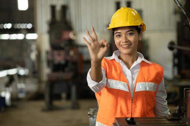 Asiatische arbeiterinnenhand zeigt ok oder gute arbeit erledigt kein problem zeichen in der arbeitsfabrik.