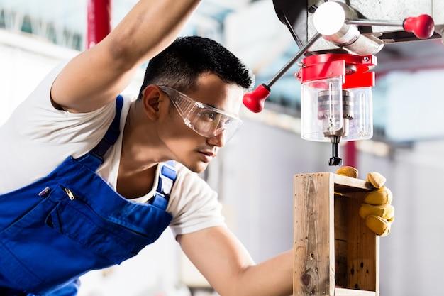 Asiatische arbeitskraft auf bohrgerät in der produktionsfabrik