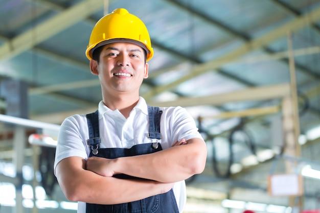 Asiatische arbeitskraft in einer fabrik oder in einer industrieanlage